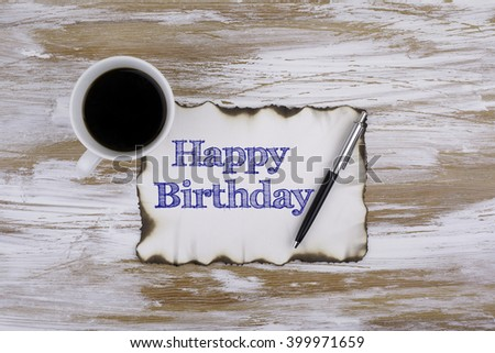 On the table a piece of paper and text - Happy Birthday - stock photo