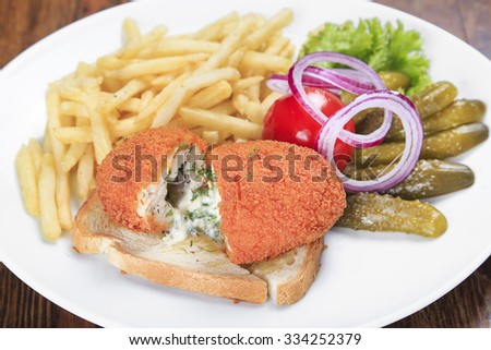 on the table a plate of chicken Kiev with fried potatoes, pickled cucumber, pickled tomatoes, onions. top view - stock photo