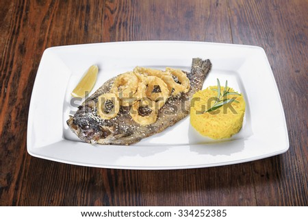 on the table a plate of grilled fish trout with lemon, fried onion rings, with sesame seeds and as a garnish rice and rosemary. - stock photo