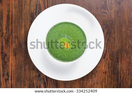 on the table a plate of spinach soup with quail egg, top view - stock photo