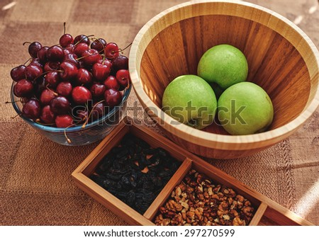 On the table is a form in which lie the nuts and raisins, close to the deep A wooden utensils which are apples, ripe cherries in a large glass bowl - stock photo