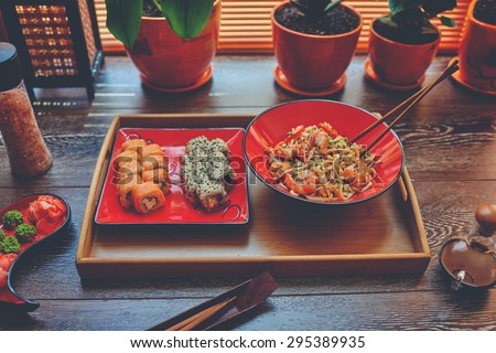 On the table is a wooden dressing on it two red plates with Japanese noodles with shrimp and sushi. Lunch in the office Sushi and Japanese rice noodles to order - stock photo