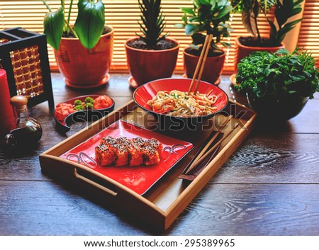 On the table is a wooden dressing on it two red plates with Japanese noodles with shrimps and prawns sushami - stock photo