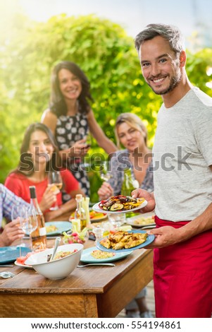On the terrace in front of the table where his friends are gathered a handsome man with gray hair presents to the camera the dishes of meats and vegetables he has just prepared. Shot with flare