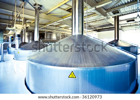 On the territory of brewer's plant, view to blue steel fermentation vats - stock photo