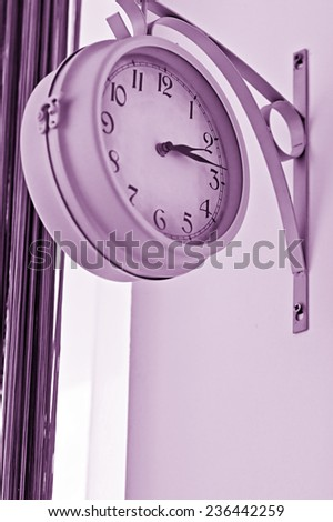 On the wall hang a clock that shows the time