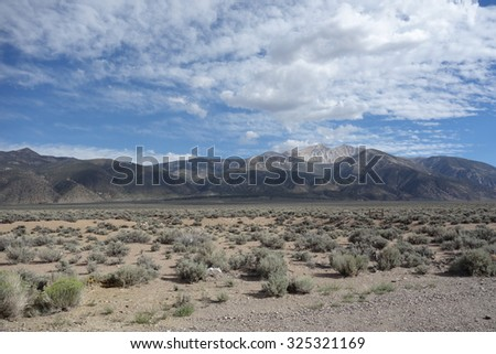 on the way from yosemite to las vegas via nevafa desert. sandy and mountains view look clouds, wildness - stock photo