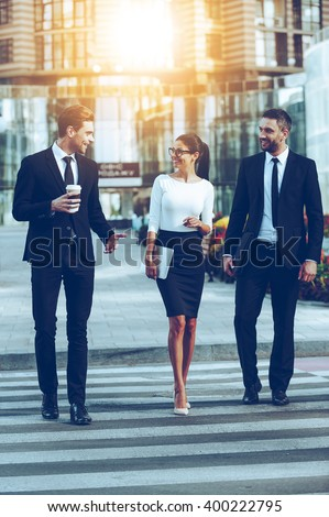 On the way to work. Full length of three smiling business people talking to each other while crossing the street - stock photo
