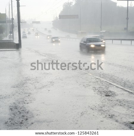 On the wet road with fast approaching cars - stock photo