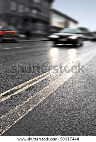 On the wet road with fast approaching cars. Photo with shallow depth of field - stock photo