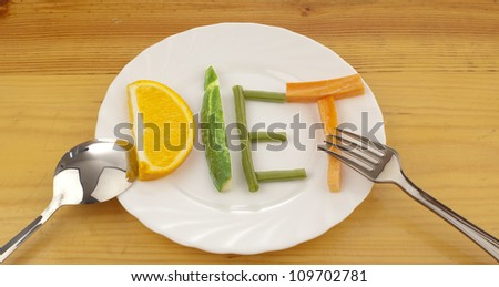on varnished wooden table is a white plate with laid out on her word - diet - composed of slices of different fruits and vegetables - stock photo