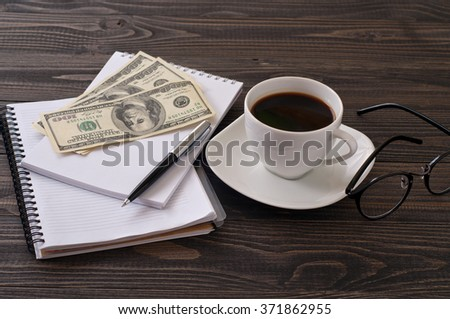 On wooden office desk, stack notepads, pen, cup of coffee, glasses and money. top view with copy space - stock photo