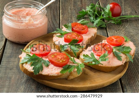 On wooden plate of bruschetta with salmon butter, capelin caviar, cherry tomatoes and parsley, jar with salmon butter and capelin caviar. Selective focus - stock photo