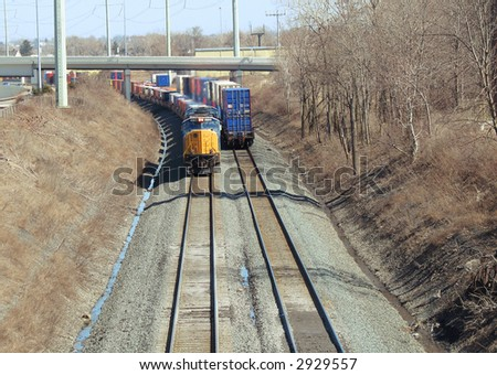 Oncoming freight train passing a retreating train on a curve - stock photo