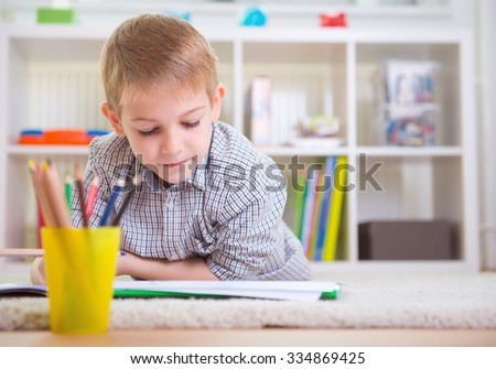 One adorable boy draws on floor at home - stock photo