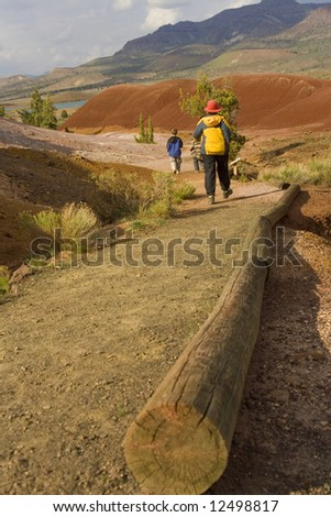 One adult and two children hike along a path near the Painted Hills in Oregon. - stock photo