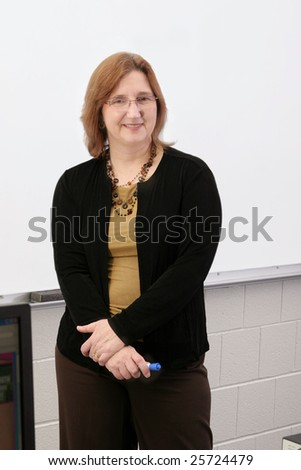 one adult female teacher pointing to a blank whiteboard - stock photo