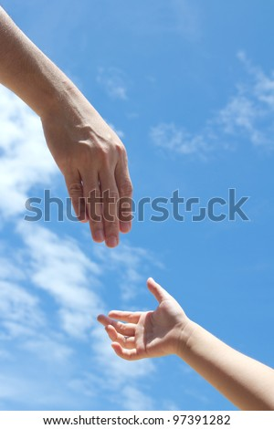 One adult hand reaches out to help child hand in need - stock photo