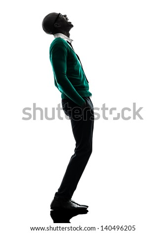 one african  black man standing looking up  laughing in silhouette studio on white background - stock photo