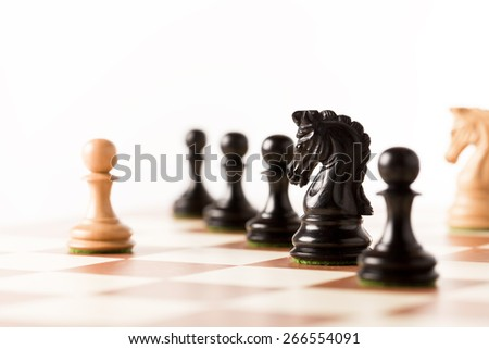 One against all - a white pawn on a chessboard with black chess pieces - stock photo