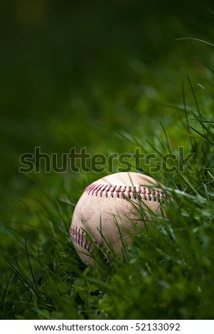 One aged and worn baseball sitting in the green grass. - stock photo