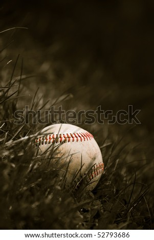 One aged and worn grungy baseball sitting in the green grass in sepia tone. - stock photo