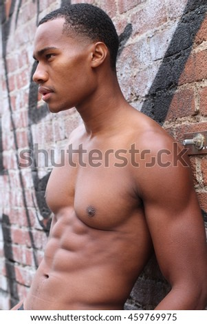 One amazing African man with muscular male sensual topless body with strong cool 6 pack abdominal and athletic chest dressed in underpants posing in profile closeup on graffiti wall background
