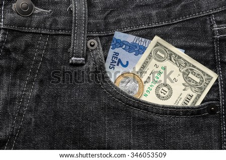 One american dollar with brazilian Real money inside a jeans pants pocket