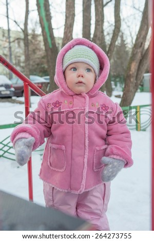 One and a half year-old girl in woolen mittens stares, standing near the hill. Winter. - stock photo