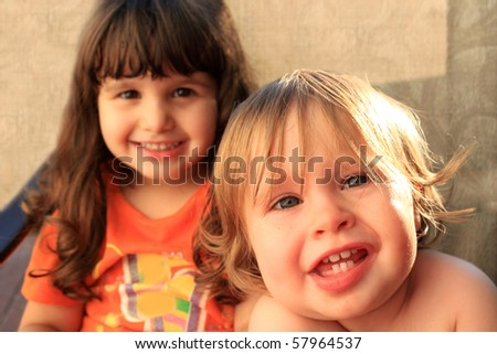 One and three year old girls sitting and smiling - stock photo