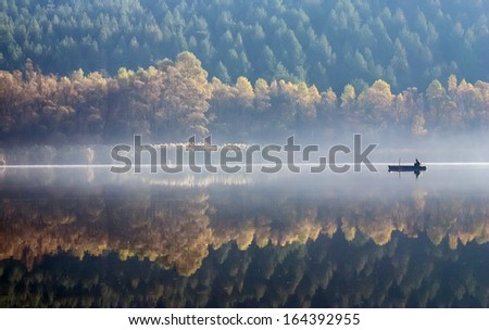 One angler fishing on a misty lake. - stock photo