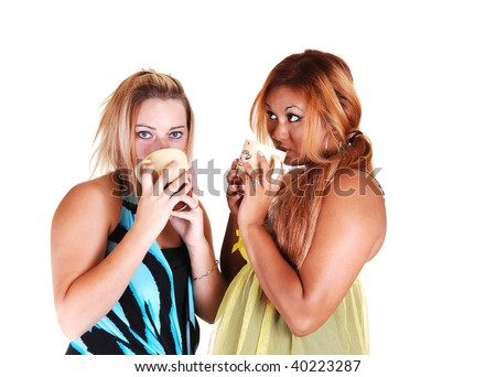 One Asian and one Caucasian woman standing together holding a cup of and having a nice shat together, on white background. - stock photo