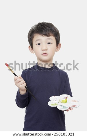 one asian boy child holds painting brush and colour palette with white background