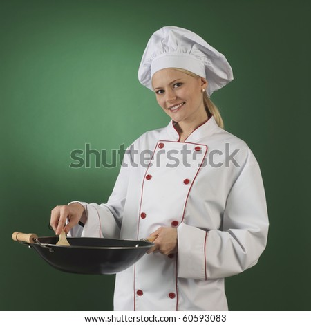 one atractive cook, she is wearing professional uniform and standinga wok