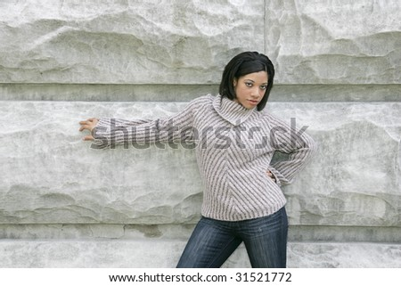 one attractive ethnic model against a stone wall outdoor portrait