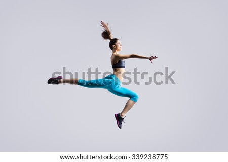 One attractive gorgeous young fit modern woman in blue sportswear with ponytail warming up, working out, dancing, jumping, full length, studio image on gray background - stock photo