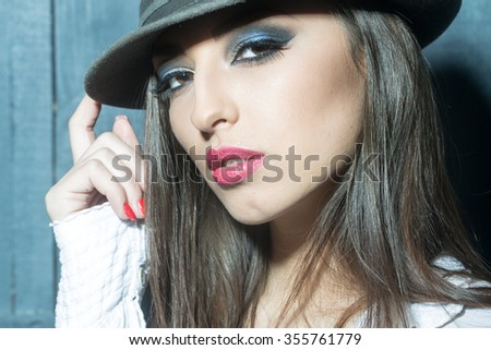 One attractive sensual fashionable young brunette pensive woman with bright makeup and beautiful hair in white blouse holding hat with hand in studio on wooden wall background, horizontal picture - stock photo