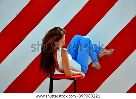 One attractive sensual sexy stylish glamour young brunette woman in blue jeans and summer t-shirt and fashionable shoes sitting on bar chair on striped red and white wall background - stock photo