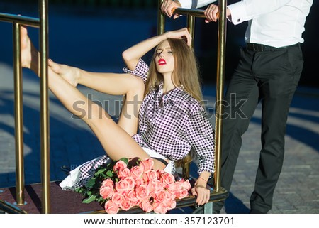One attractive sensual straight fashionable stylish dreaming young lady with long slim legs in black and white blouse sitting on hotel luggage pole with bouquet of pink rose flowers outdoor sunny day - stock photo
