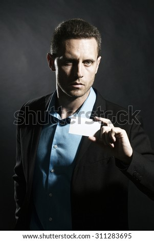 One attractive serious unshaven young business man in jacket and blue shirt holding white calling card in hand looking forward standing on black studio background copyspace, vertical picture - stock photo