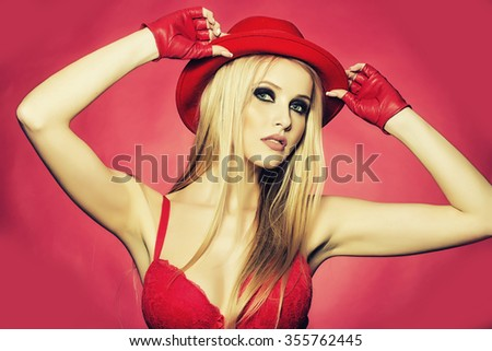 One attractive sexual sensual young blonde woman with long hair in red cowboy hat gloves and bra as strip dancer on pink backdrop, horizontal picture - stock photo