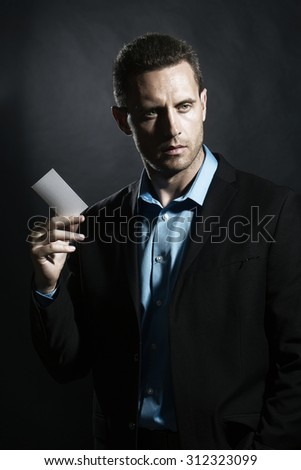 One attractive sexual unshaven young boy in jacket and blue shirt holding white business card in hand looking forward standing on black studio background copyspace, vertical picture - stock photo