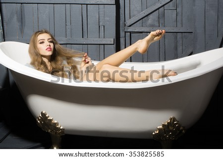 One attractive sexy sensual naked young smiling woman with long hair and straight slim beautiful body lying in white bath tub indoor on wooden background, horizontal picture - stock photo