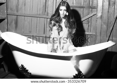 One attractive sexy sensual playful young woman with long hair in knitted cloth sitting on white bath tub playing with soap foam indoor on wooden background black and white, horizontal picture