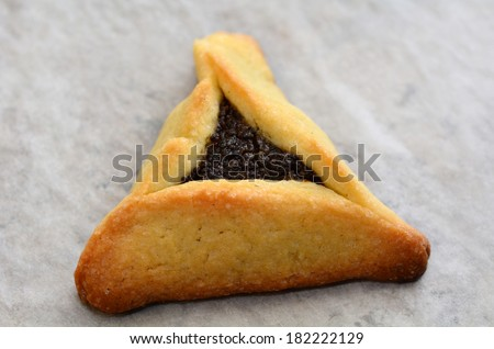One backed Hamentashen, Ozen Haman, Purim cookie for the Jewish holiday Purim. Isolated on baking paper. (Copy space) - stock photo