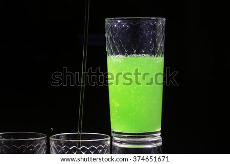 One beautiful bright green colored tasty sweet alcoholic cocktail shooter shot in white glass for night party made of tequila drink fresh lime juice and mint on black background closeup, horizontal - stock photo