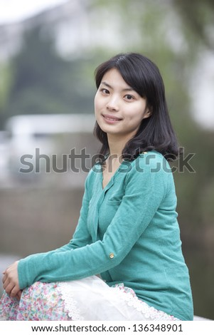 One beautiful Chinese student sit in campus - stock photo