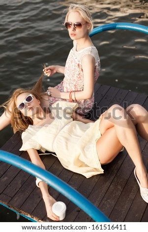 one beautiful girl lies on her girlfriend's knee holding to-go cup while her friend plays with her hair - stock photo