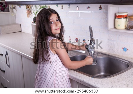 One beautiful middle eastern little girl with pink dress and long dark brown hair and eyes on white kitchen,helping parents to wash dishes and drinking water and smiling looking at camera studio shot.