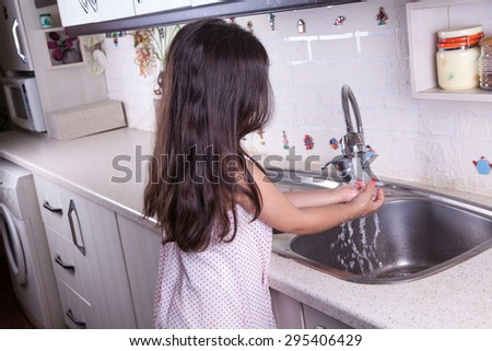 One beautiful middle eastern little girl with pink dress and long dark brown hair and eyes on white kitchen, helping parents to wash dishes and drinking water and smiling.  studio shot.